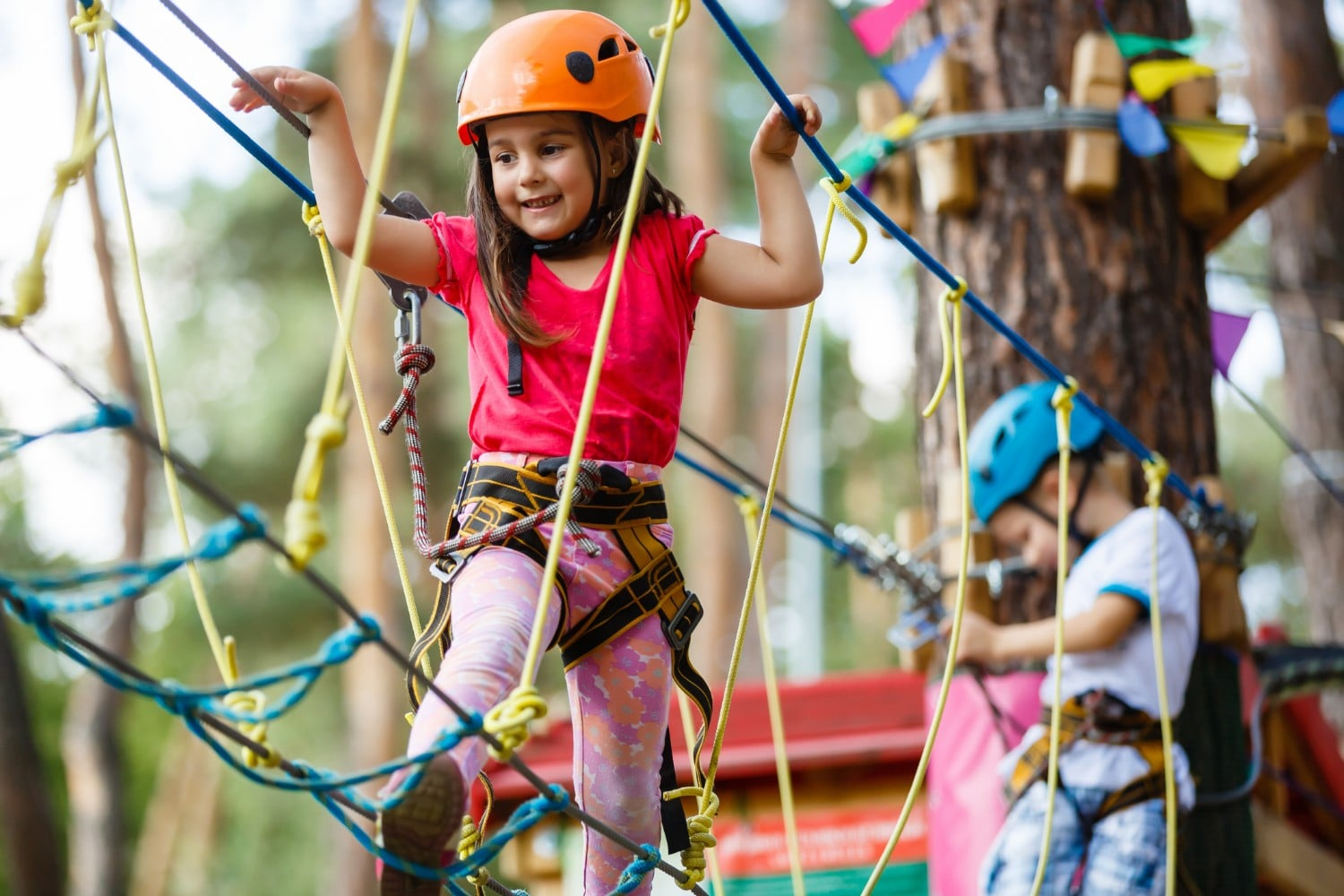 Little girl climbs on ropes course