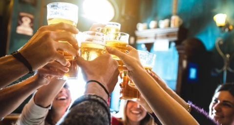group of people holding beer glasses up